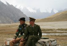Chinese and Pakistani guards sitting on a rock at the Khunjerab Pass