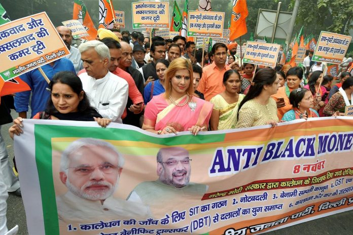 BJP workers display a banner during their Anti-black Money Day rally to mark the first anniversary of 'Demonetisation' announcement in New Delhi on Wednesday.