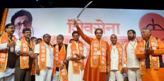 Shiv Sena President Uddhav Thackeray brandishes a sword at the party's national executive meeting at NSCI Worli in Mumbai