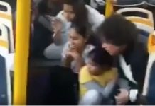 A woman and children crouched on the floor of the GD Goenka World School bus