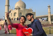 A young couple takes a selfie in front of the Taj Mahal replica