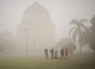 People stand in a park amid heavy dust and smog in Delhi
