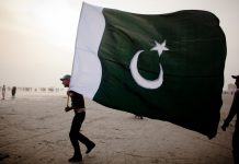 A man walks with a Pakistan National flag | Daniel Berehulak/Getty Images