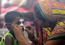 A woman looks after her child at the encephalitis ward of the the Baba Raghav Das Hospital, Gorakhpur
