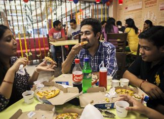 Customers eat at a Domino's Pizza outlet, operated by Jubilant Foodworks Ltd.
