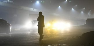 A pedestrian is silhouetted as traffic moves along a road shrouded in smog in New Delhi