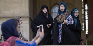 Iranian women watch as a girl clicks selfie at the Chehel Sotun palace in Isfahan, Iran