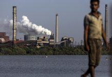 A laborer walks near the JSW Steel Ltd. manufacturing facility in Dolvi, Maharashtra. Photographer: Dhiraj Singh/Bloomberg