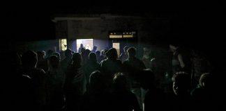 People gather outside a dairy shop in Fateh Nagla, Uttar Pradesh | Prashanth Vishwanathan/Bloomberg
