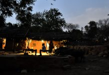 People sit outside a home at dusk in Kraska village, Rajasthan | Anindito Mukherjee/Bloomberg