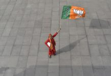 A man holds a flag of Bharatiya Janata Party at the courtyard of the party's headquarters in New Delhi (REPRESENTATIONAL IMAGE) | Anindito Mukherjee/Bloomberg