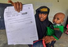 A woman shows an NRC acknowledgment receipt in Morigaon, Assam | PTI