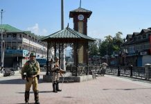 Security personnel guard during the strike call given by separatist leaders against urban local bodies elections, at Lal Chowk in Srinagar
