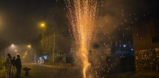Revelers watch a firework during Diwali celebrations in Delhi | Prashanth Vishwanathan/Bloomberg