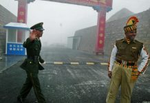 A Chinese soldier and an Indian soldier stand guard at the Chinese side of the Nathu La border | Getty Images