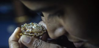 An employee uses a loupe to inspect a diamond studded gold jewelry piece