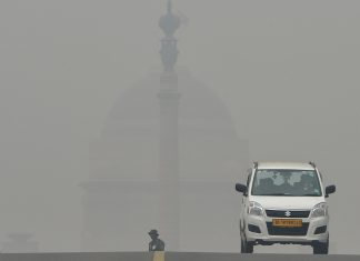 Commuters drive through heavy smog at Rajpath
