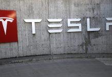 A company logo hangs outside a Tesla Inc. store in Bern, Switzerland