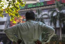 A man stands in front of an electronic ticker board showing stock information figures outside the Bombay Stock Exchange (BSE) in Mumbai