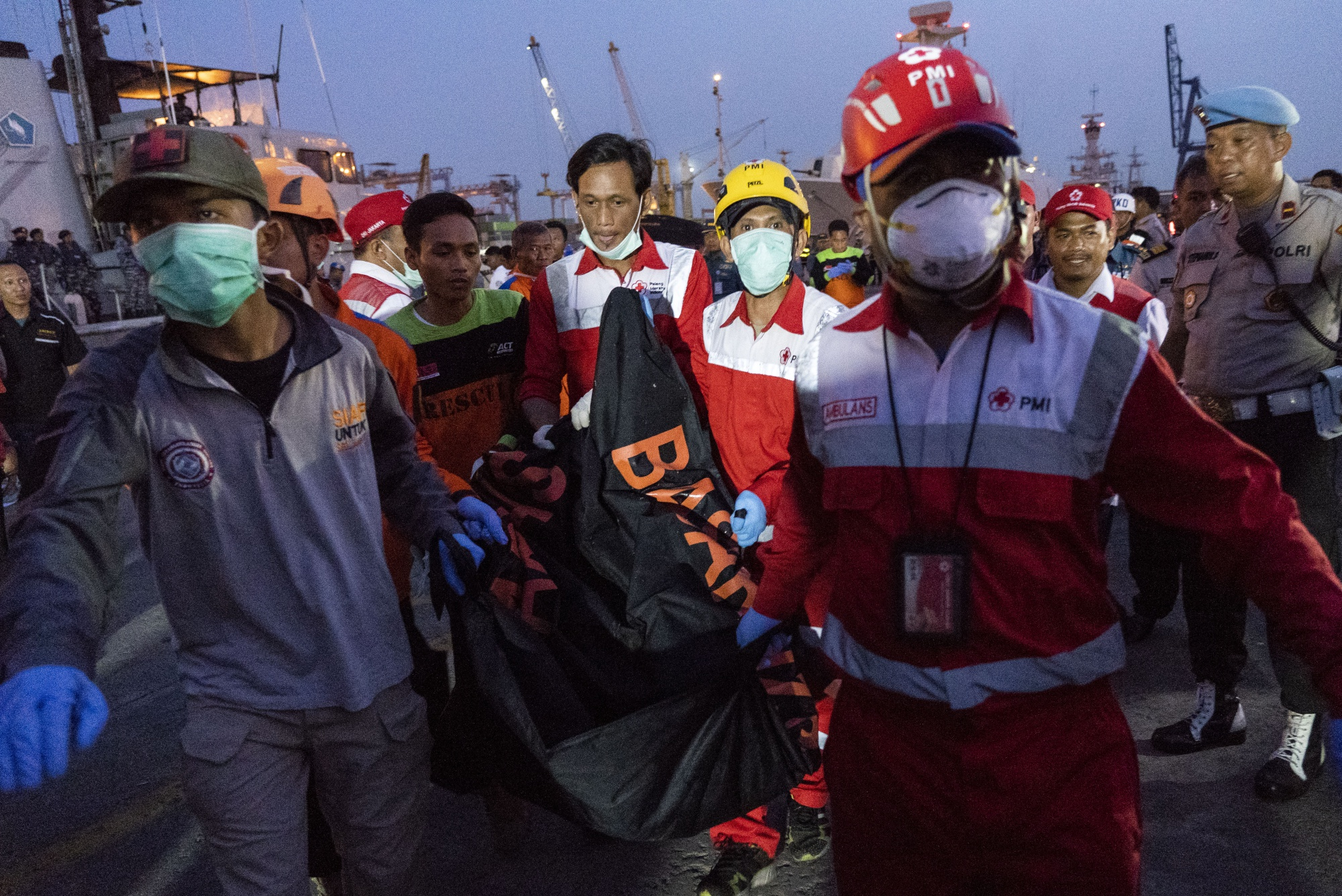 Search and rescue team members carry a body recovered from the crash | Rony Zakaria/Bloomberg