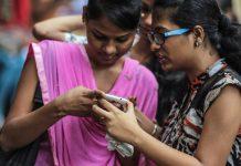 Women in Mumbai look at a phone | Dhiraj Singh/Bloomberg