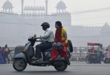 People ride a scooter along a road shrouded in smog in New Delhi