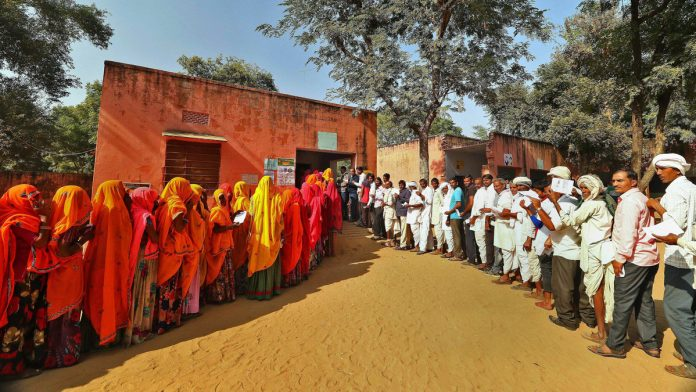 Voters stand in queues outside a polling station in Jaipur | PTI