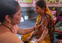 A health worker immunises a pregnant woman at a health centre in Aurangabad, India