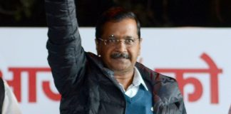 Delhi Chief Minister Arvind Kejriwal waves at his supporters during a public meeting, in the walled city area of New Delhi