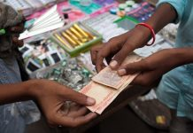 A vendor hands Indian rupee banknotes to a customer at a stall in Chauta Bazaar in Surat, Gujarat