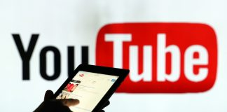 A man is seen as a silhouette as he checks a mobile device whilst standing against an illuminated wall bearing YouTube Inc.s logo in this arranged photograph in