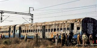 In this Feb 19, 2007 file photo, police inspect the burnt coaches of Samjhauta Express at Deewana village near Panipat