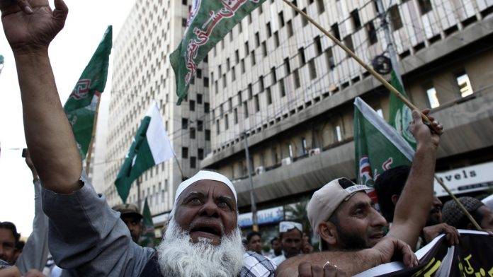 Demonstrators wave flags during an anti-India protest in Karachi, Pakistan