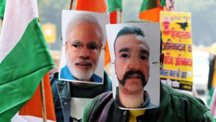 People wear masks of IAF pilot Abhinandan Varthaman and PM Narendra Modi during a rally in New Delhi | T. Narayan/Bloomberg