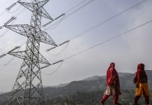 Woman walk past a transmission tower in Jammu and Kashmir | Dhiraj Singh/Bloomberg