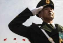 A member of the Chinese People's Armed Police salutes in Tiananmen Square following the first session of the 13th National People's Congress (NPC) in Beijing