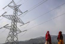 Woman walk past a transmission tower in Rajouri district, Jammu and Kashmir  Dhiraj Singh/Bloomberg