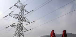 Woman walk past a transmission tower in Rajouri district, Jammu and Kashmir |Dhiraj Singh/Bloomberg