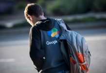 A pedestrian wearing a sweatshirt with a Google Inc. logo waits for a bus in front of the company's headquarters in Mountain View, California, U.S