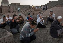 Uyghur men perform prayers for ancestors at a cemetery before the Corban Festival