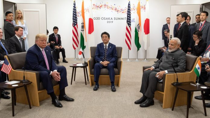 US President Donald Trump, left, Shinzo Abe, Japan's prime minister, center, and Narendra Modi at G-20 summit in Osaka, Friday| Photo: Carl Court | Bloomberg